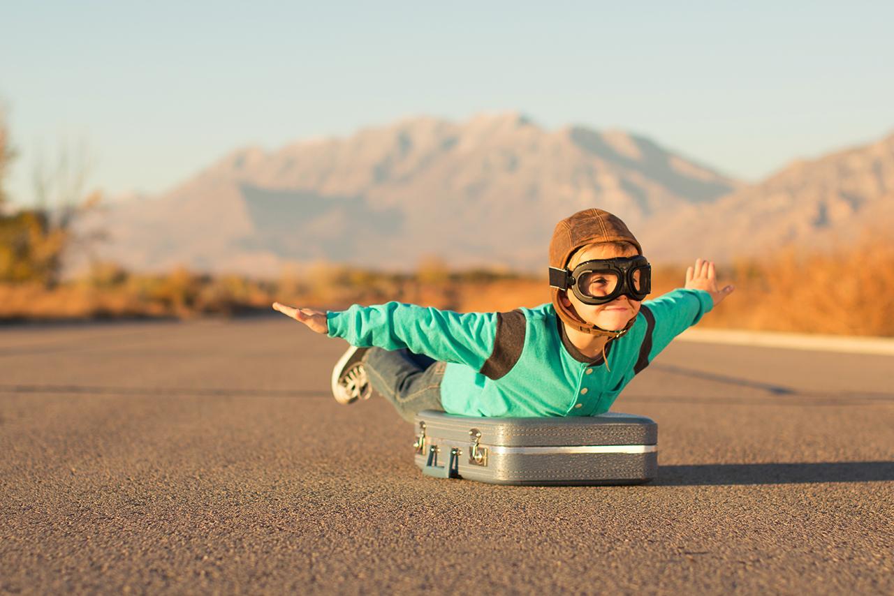 Garçon faisant l'avion allongé sur sa valise, sur une route