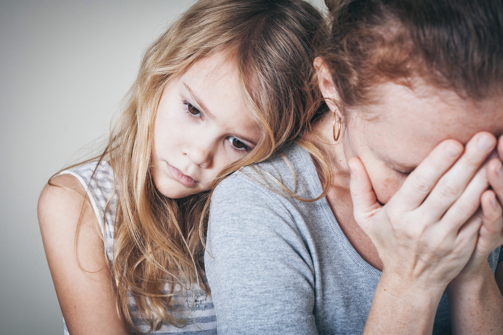 Mère le visage dans les mains et sa fille pensive